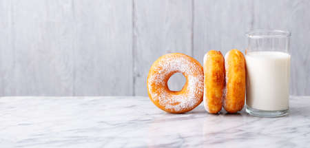 Donuts with glass of milk on marble table. Grey background. Copy space.