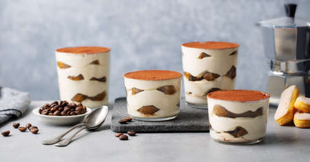 Tiramisu dessert in glass on table. Confectionery shop menu. Grey background.