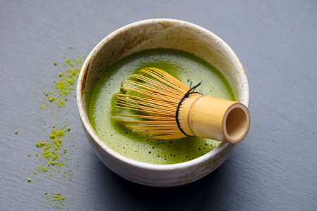 Matcha green tea cooking process in a bowl with bamboo whisk. Grey background. Close up. Stock Photo