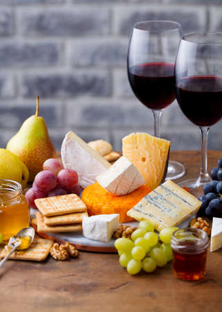 Cheese assortment with red wine in glasses. Stone and wood background.