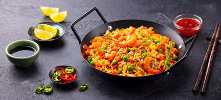 Stir fry rice with vegetables and shrimps in black iron pan. Slate background. Close up.