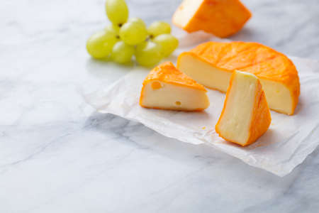 Cheese with washed orange rind with grape. French or German product. Marble background. Copy space.