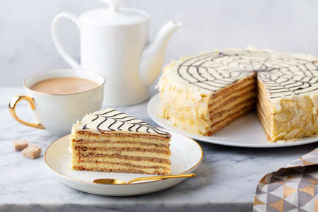 Traditional Hungarian Esterhazy cake, torte with cup of coffee. Marble background. Close up.