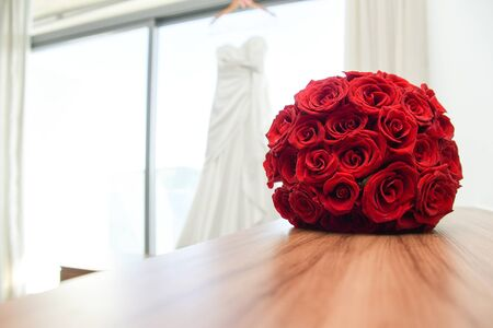 Red wedding bouquet with dress hanging in the background