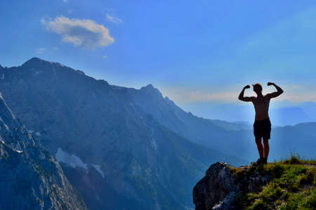 Young man posing on the edge of rock. Beautiful mountains in the background.
