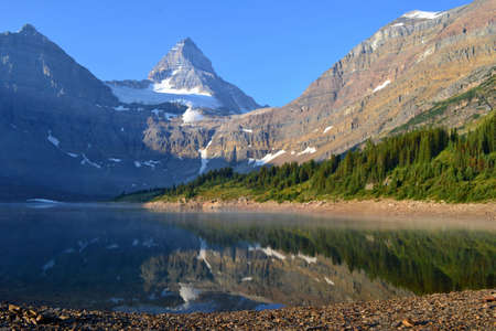 Cold sunny morning in Assiniboine Provincial Park. Lake in front with rolling fog, Mount Assiniboine covered with snow in towering over whole scenery.