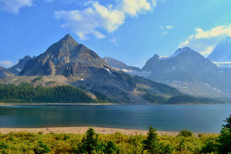 Mount Assiniboine Provincial Park, Canada. Beautiful High Mountains with Glacier, Blue Lake, Green Grass and Trees, White Clouds. 写真素材