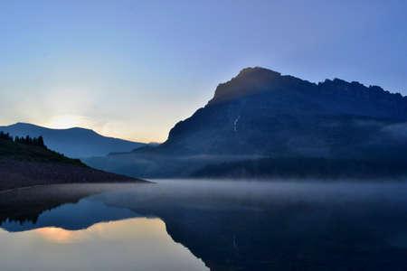 Kalter sonniger Morgen im Assiniboine Provincial Park. Sonnenaufgang, Nebel auf dem See, hohe Berge.