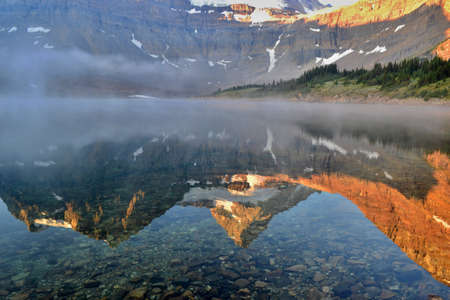 Cold sunny morning in Assiniboine Provincial Park. Reflection of Mount Assiniboine covered with snow in lake, fog.