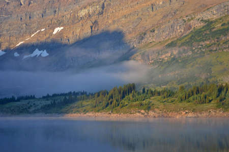 Cold sunny morning in Assiniboine Provincial Park. Lake in front with rolling fog, Mount Assiniboine massif covered with snow behind the trees. 写真素材