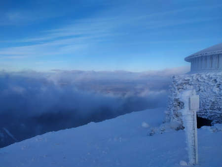Beautiful sunny day in Krkonose Mountains. The highest peak of Snezka with its frozen weather station. Clouds in the valley.