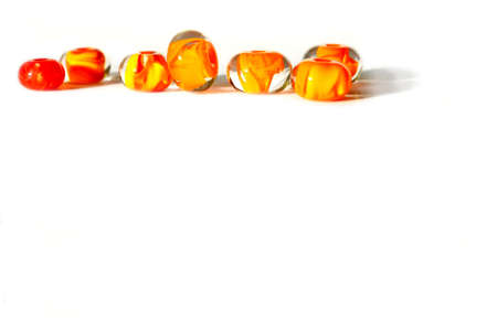Beautiful colorful cheerful background made of handmade lampwork beads with flames inside. Beads are isolated on a white background, situated top left. Suitable for text insert. Stock Photo
