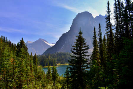 Beautiful sunny day in Mount Assiniboine Provincial Park. Mount Assiniboine covered with glacier, Blue Lake, Lush Forrest, High Mountains.