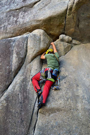 Young man climbing a rock in Squamish in Burgers and Fries leading the rope.