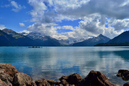 Beautiful blue Garibaldi Lake surrounded by high mountains with glaciers. Mysterious white and gray clouds, blue sky. An island with stone pyramids. Rocky lake bank. Stock Photo