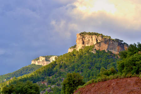 Orange massive rock on green mountainside covered with trees, climbing sector. Blue sky with white clouds. Beautiful nature, mountains. Siurana, Catalonia, Spain. 版權商用圖片