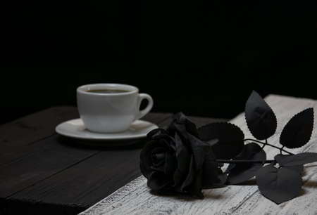 White coffee cup on black background and black rose on white background