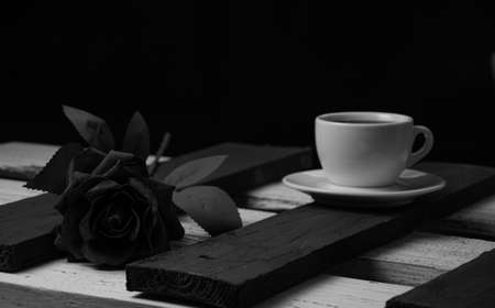 White coffee cup on black boards and black rose on white boards