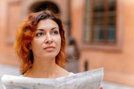 Pretty young female tourist with a map discovering history foreign city, looking to monuments. Woman holding city map. Solo girl travel in Europe. Foto de archivo