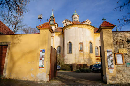 Yellow baroque church of the Holy Trinity near Discalced Carmelite Monastery in old historic center of medieval royal town Slany in sunny day, Central Bohemia, Czech Republic, December 27, 2020