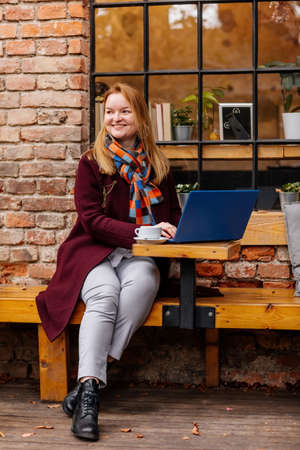 Attractive young elegant business woman spending time at cafe, drinking coffee and working on her laptop. Romantic female blogger smile near the window outdoors. Freelancer thinking about new ideas. Archivio Fotografico