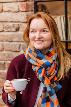 Close up portrait of attractive young woman sitting at outdoor terrace coffee shop with a cup of coffee. Stylish caucasian girl wearing warm knit clothes at open air, looking at camera smiling Archivio Fotografico
