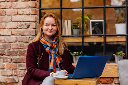 Attractive young elegant business woman spending time at cafe, drinking coffee and working on her laptop. Romantic female blogger near the window outdoors. Freelancer thinking about new ideas. Archivio Fotografico