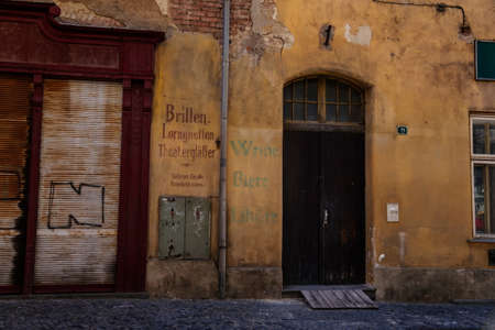 Narrow picturesque street with renaissance and baroque historical buildings, peeling plaster, inscriptions in German, paving stone, sunny day, Zatec, Bohemia, Czech Republic, April 04, 2021