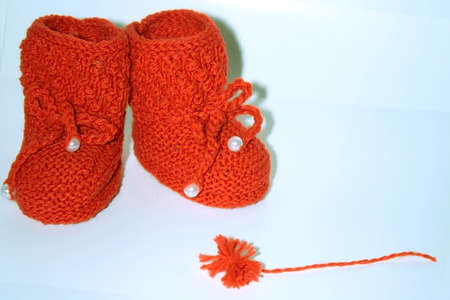 Red knitted baby booties , a red pompon of yarn on a white background