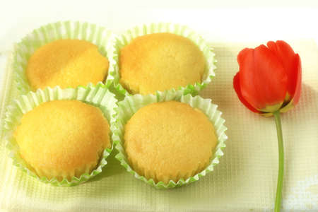 Freshly baked homemade muffins in paper green molds on a beige napkin on a wooden table with a red tulip flower.
