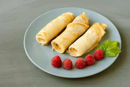 A three rolled pancakes with raspberries and mint on a gray plate on a gray texture background.
