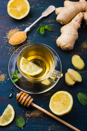 Cup of Ginger tea with lemon and honey on dark blue background, top view Banco de Imagens