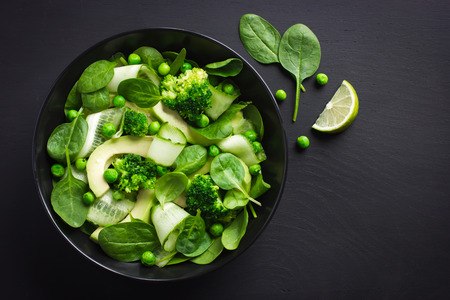 Healthy food. Fresh green salad on black background, top view