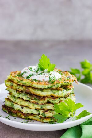 zucchini fritters, vegetarian zucchini pancakes, served with fresh herbs and garlic yogurt sauce, selective focus Banco de Imagens