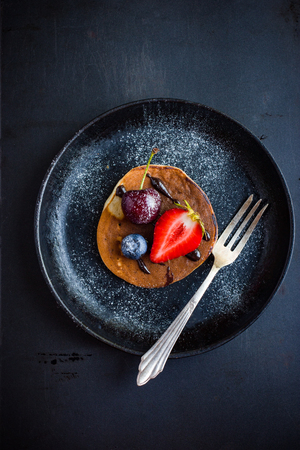 pancake with fresh berries and chocolate sauce on  black plate, top view