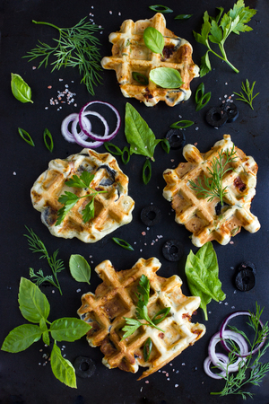savory waffles with cheese, ham, olives and herbs on black background, top view