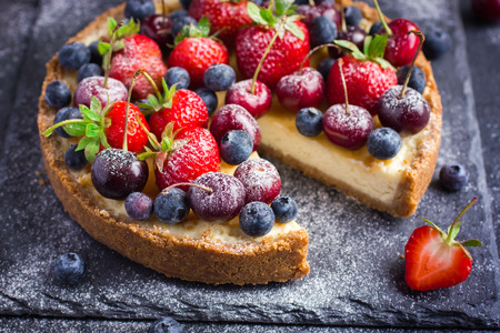 cheesecake with fresh summer berries. Selective focus. Dark background Stock Photo