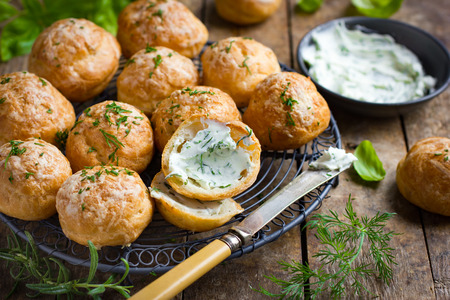 Gougeres with herb cream cheese. Traditional french cheese choux buns. wooden background.