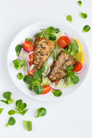 roasted mackerel fish with fresh salad, white background, top view