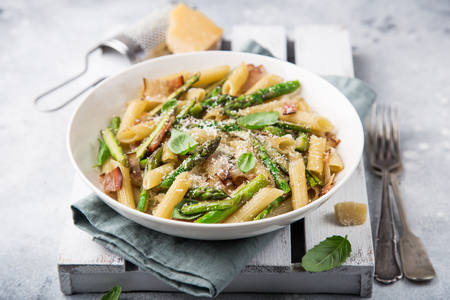 asparagus and bacon penne pasta with parmesan cheese in white bowl, selective focus