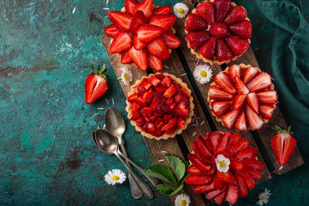 strawberry tartlets  on green background, top view, copy space
