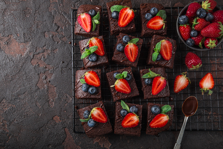 chocolate brownies  with fresh strawberry and blueberry on dark background, top view