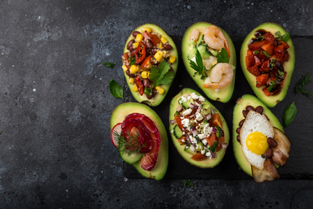 avocado halves stuffed with different toppings on dark background, top view, copy space Zdjęcie Seryjne