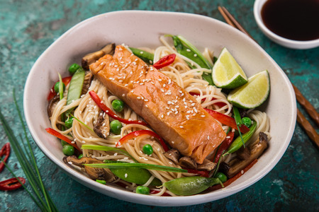 salmon with noodles and vegetables in asian style , selective focus
