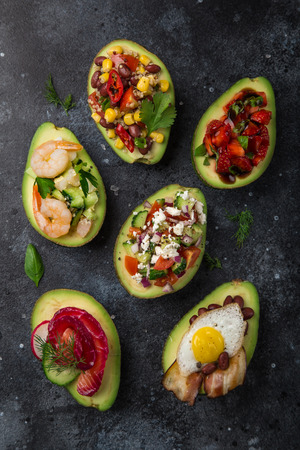 avocado halves stuffed with different toppings on dark background, top view Zdjęcie Seryjne