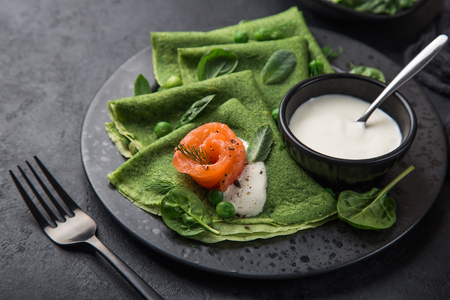 spinach crepes with smoked salmon and yogurt sauce on black plate, dark background, selective focus