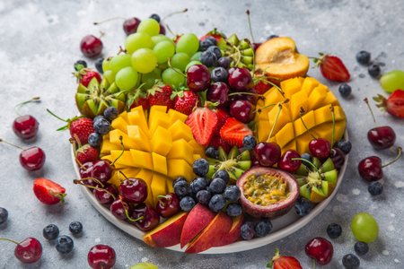 delicious fruits and berries platter.  Mango, kiwi, strawberry, grape, cherry, blueberry, peach and passion fruit, selective focus Zdjęcie Seryjne