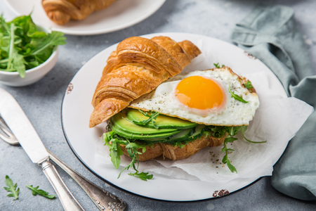 croissant sandwich with avocado, arugula and fried egg for breakfast, selective focus