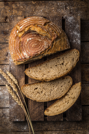 slices of fresh baked sour dought bread on rustic wood background, top view