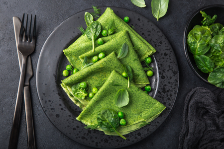 spinach crepes with green peas on black plate, dark background, top view